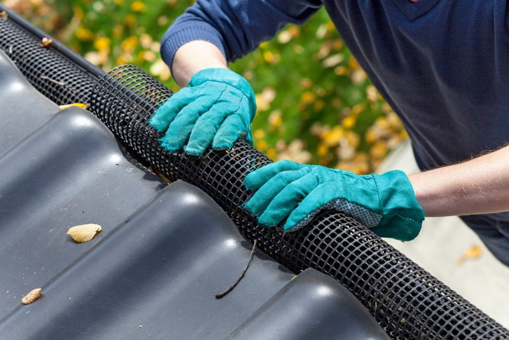person applying gutter guards